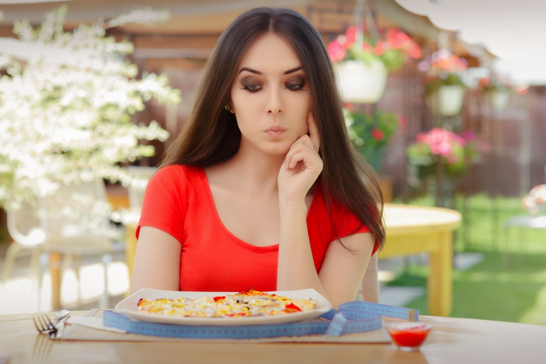 37428015 - young woman thinking about eating pizza on a diet